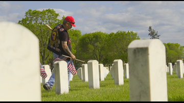 Volunteers place flags at Fort Snelling