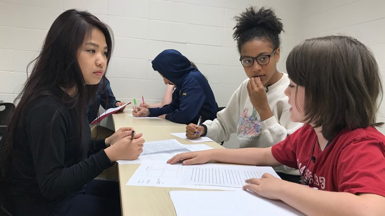 Anna Huynh (left) and Nia Diaby work on a group project with 10-year-old Elliott Tanner at Normandale Community College.