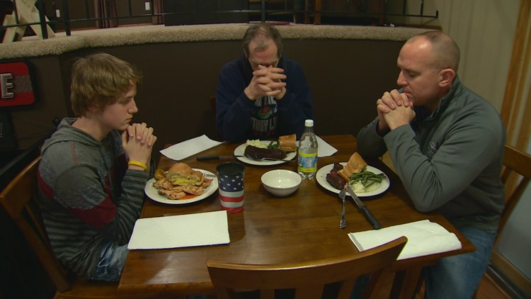 William Tentis (middle) leads a dinner prayer at the home of Eric Reetz and his son Ethan