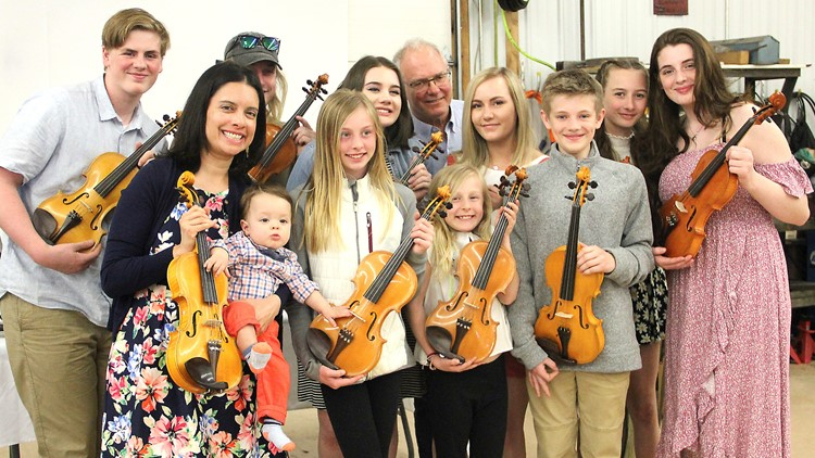 The grandchildren of Gene Van Alstine hold the 10 violins he made for them.