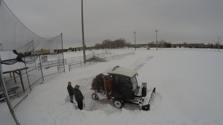 City workers from Elk River clear snow from a baseball diamond for the running of the Sandlot Marathon