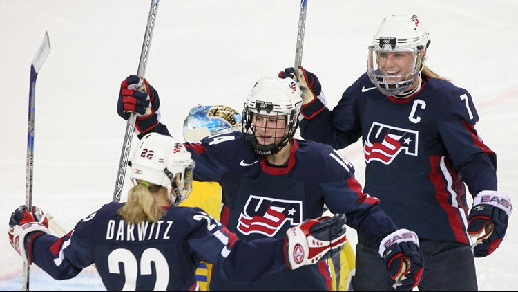 Natalie Darwitz (L), Kelly Stephens (C) and Krissy Wendell celebrate their second goal during the ice hockey women's semi-final USA-Sweden at the 2006 Winter Olympics, 17 February 2006. (Photo credit: DON EMMERT/AFP/Getty Images)