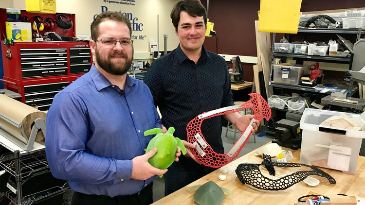 U of M Ph.D. student David Fay (left) holds a scale model of Seemore the sea turtle, while undergrad Tom Skahen holds one of the backpack prototypes they designed to help Seemore.