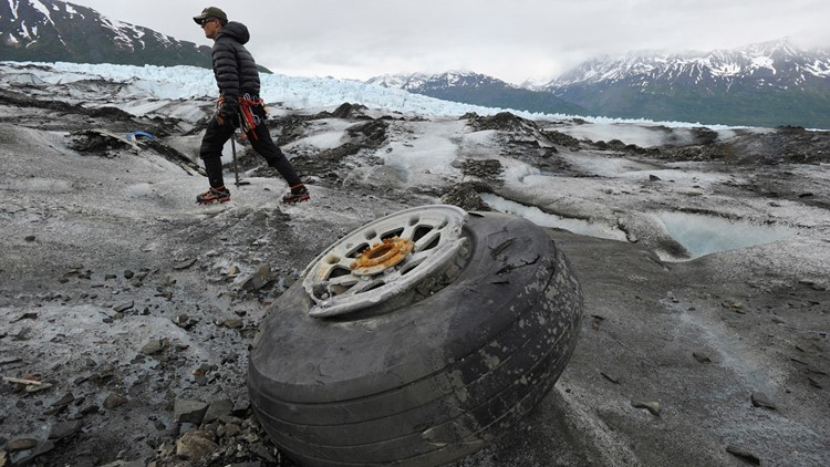 An airplane wheel rests on the surface of Colony Glacier in Alaska