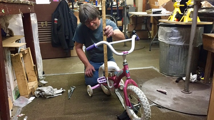Jack Carlson measuring the seat height on a bike he rebuilt