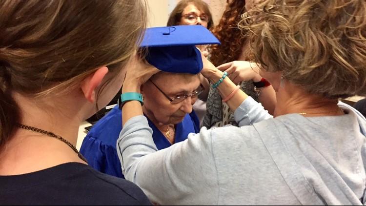 The great grandchildren of Esther Begam help her with her graduation cap