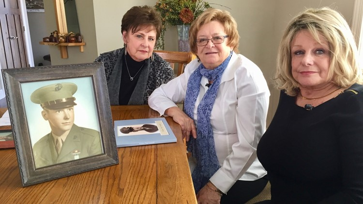 Left to right, Colleen Page, Diane Finnemann and Jacquie Krismer pose with a picture of their brother, Skip Schmidt