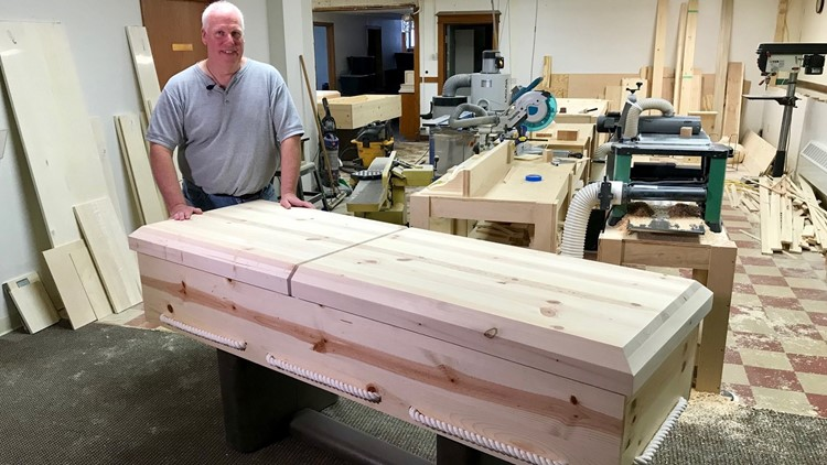 Mark Coen displays one of his hand-built pine caskets