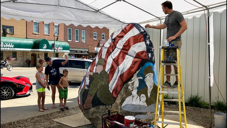 Artist Bubba Sorensen paints a Freedom Rock while a mother and her children look on