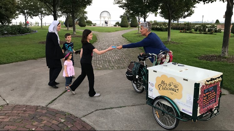 Mrs. Delicious gives away ice cream to a young customer