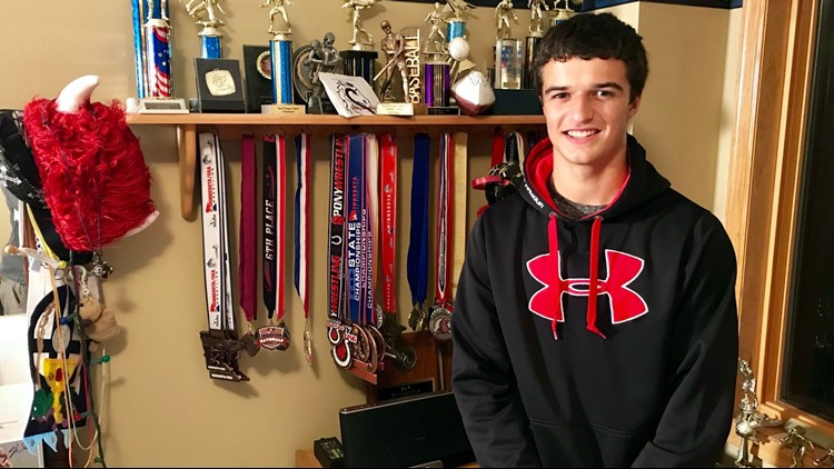 Trey Kruse poses with the trophies and medals he's won a multi-sport athlete