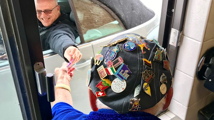 Art Mason's ball cap displays some of the 1,000 pins he's received from his drive-thru customers.