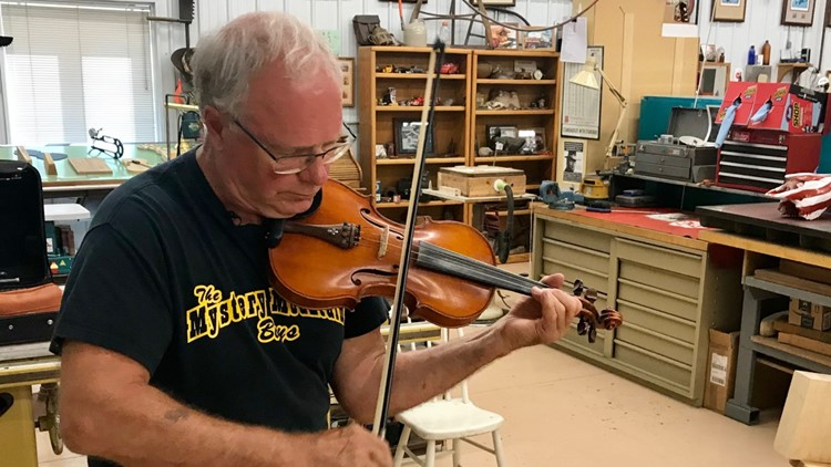 Gene Van Alstine plays fiddle in his workshop