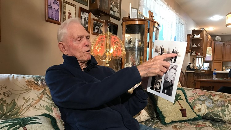 WWII veteran Jim Clermont points to pictures of himself as a young Navy sailor