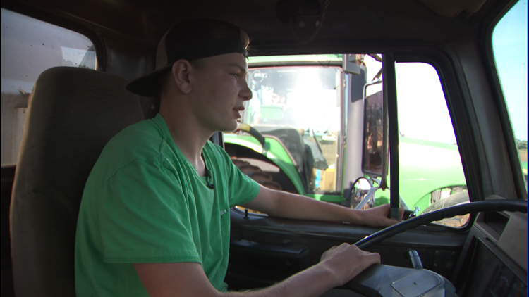 16-year-old Bennett Edling drives a truck alongside the harvester operated by his Uncle Mark.