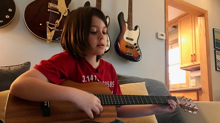Ten-year-old college student Elliott Tanner relaxes at home with his guitar.