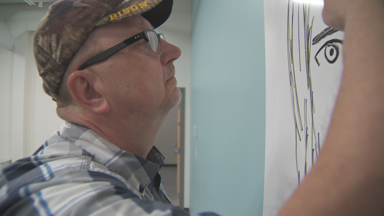 Janitor Myron Peterson works on one of his whiteboard sketches