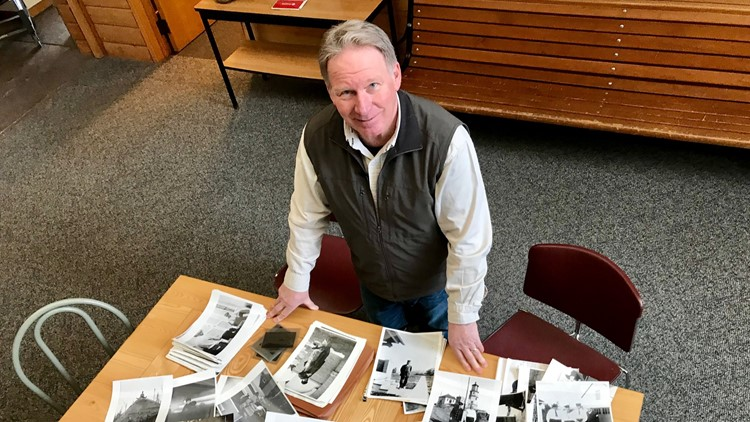 Lee Radzak poses with photos of some of the 39 lighthouse keepers who came before him at Split Rock.