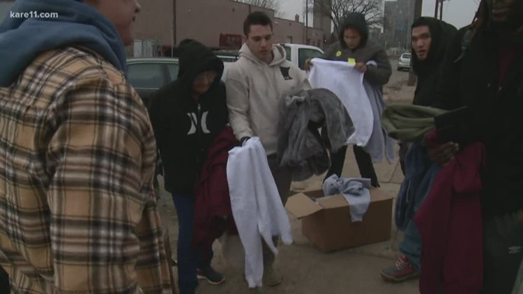 local business passes out hoodies at mpls homeless camp